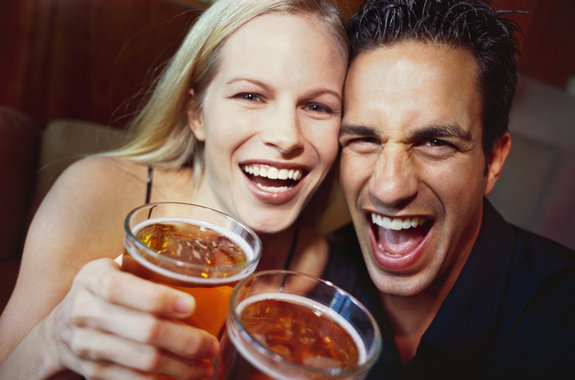 close-up of a young couple laughing with glasses of beer in their hands